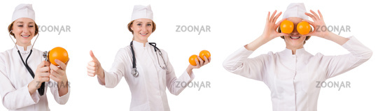 Pretty female doctor holding orange isolated on white