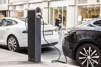 Charging modern electric car on the street as future of automotive industry.
