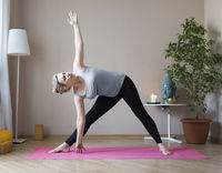 Middle aged woman doing yoga indoors