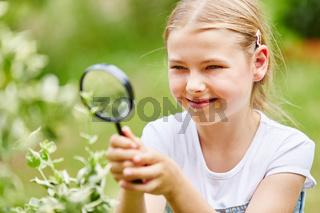 Mädchen mit Lupe im Garten