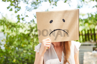 Frau hat Gesicht im Pappkarton mit Trauer Gesicht