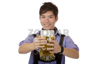 Lachender Asiate hält einen vollen Oktoberfest Bierkrug (Mass)