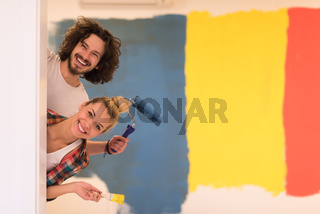portrait of a couple painting interior wall
