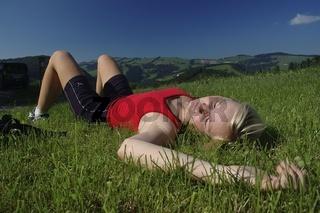 Blonde Frau (22) liegt in der Wiese und geniest nach einer Wanderung die sommerliche Landschaft