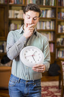 Young man scared of time holding clock