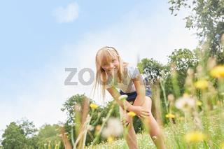 Blondes Mädchen spielt auf einer Wiese