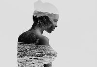 Silhouette of a naked woman combined with a mountains. Double exposure, isolated on a white background. Black and white
