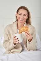 Beautiful woman having breakfast in bed
