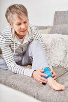 Seniorin kühlt Verletzung am Knöchel