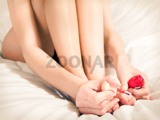 Close up woman brushing her nails in the red color