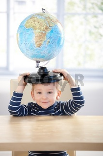 Adorable 3 year old having fun with globe smiling