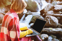Mockup image of a girl wrapped in a plaid plaid with a laptop with a blank black desktop on her lap against the background of a mountain river and large stones. The concept of freelancing in freedom from a permanent place of work and work in travels in na