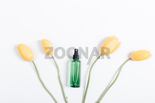 Top view of yellow tulips with green stems and a bottle of water