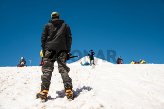 The mountaineer stands with his back and looks at the mountain and how one learns to slide along the snow slope and the glacier as well as braking with an ice ax