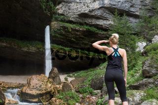 Active sporty woman under a Pericnik waterfall, Slovenia.