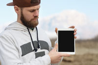 Close-up Portrait of a hipster in a brown cap in the open air holds a white tablet pc in his hands. A bearded man looks at the tablet. background blur
