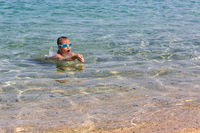 Young tourist girl in swimming sports glasses is floating in the Aegean Sea on the coast of Sithonia Peninsula