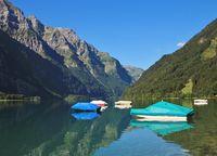 Fishing boats on lake Klontalersee, Switzerland. Glarnisch, mountain rage reflecting in the water. Summer scene.