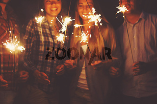 Young people with sparklers having fun on outdoor party