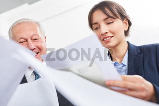 Frau und Senior schauen auf Unterlagen