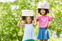 Mädchen spielen mit lustig bemalten Kartons