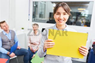 Azubi hält buntes Schild im Workshop