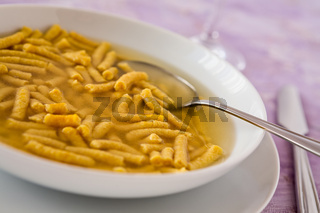 Closeup of Passatelli in broth original Italian pasta