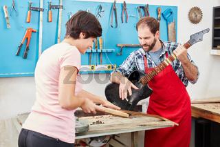 Frau als Gitarrenbauer Azubi mit Ausbilder