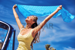 Happy woman with a hands raised against blue sky