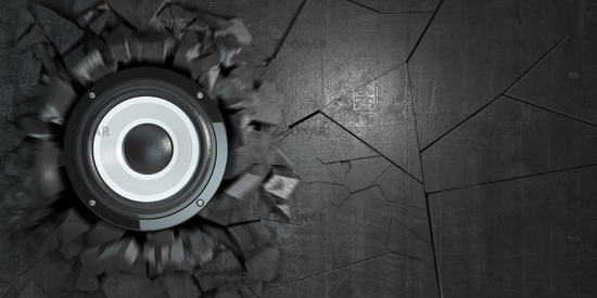 Powerful audio speakers broke concrete wall.  Explosion hole and debris. Hard rock or heavy metal energy music concept.