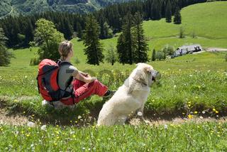 Junge Frau mit Hund beim Wandern mit Blick auf Gschwendtalm im Nationalpark Kalkalpen, Oberösterreich, Österreich
