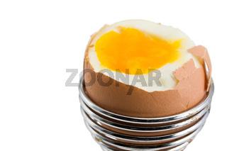braunes Ei in einem Eierbecher auf weißem Hintergrund
