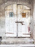 Altes hölzernes Tor in einer Wand aus Stein
