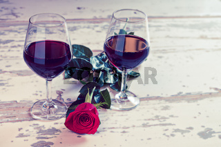 Two glasses of red wine and a rose