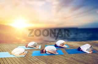 group of people doing yoga child pose outdoors