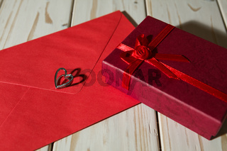 Silver heart pendant on a red envelope and gift box