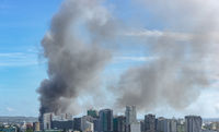 View of danger fire in city vbehind of modern buildings
