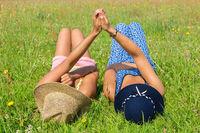 Two friends lying side by side in green grass