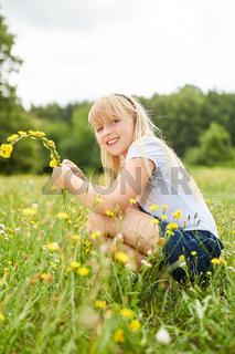 Blondes Mädchen pflückt Löwenzahn Blumen