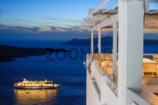 Enlighted cruise ship after sunset near Fira town at Santorini island, Greece