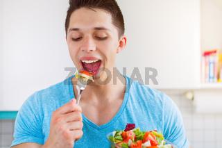 Junger Mann isst essen Salat in der Küche gesunde Ernährung vegan
