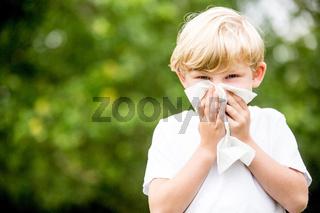 Kind mit Allergie beim Nase putzen