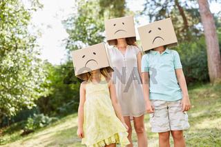 Anonyme Familie versteckt unter Pappkartons mit Trauer Gesicht