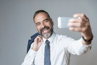 Selfie time, cheerful senior business man