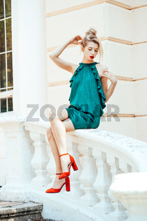 girl in green dress sits on stone handrails