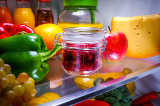 Fresh raspberries in a glass jar on a shelf open refrigerator