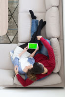 couple relaxing at  home with tablet computers