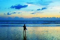 Surfer running in the ocean