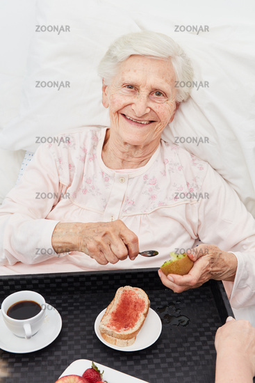 Glückliche Seniorin beim Frühstück im Bett