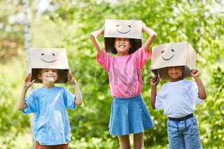 Kinder spielen mit lustigen Pappkartons